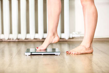 weight scale: Caucasian female legs gently tread on the floor scales