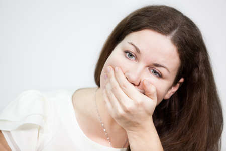 mouth closed: Caucasian young woman covering her mouth with hand, grey background