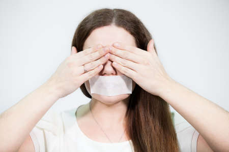 voiceless: Caucasian woman covering her eyes with hands while mouth sealed with tape Stock Photo