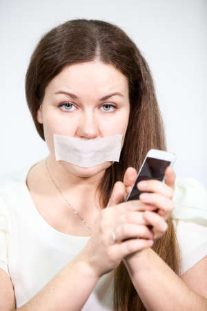 sealed: Caucasian woman with mouth sealed tape holding a cell phone in hands, grey background