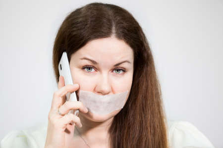 renunciation: Caucasian woman with sad eyes and mouth sealed calling mobile phone, grey background