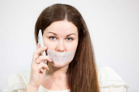 Attractive woman with tape on mouth trying to call mobile phone, grey background
