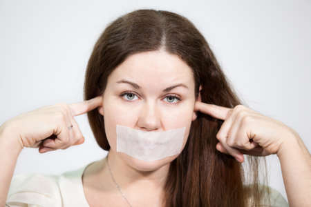 human rights: Caucasian young woman with mouth sealed and plugged ears, close-up, grey background