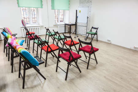 Interior of colorful room for business meeting with arranged chairs and flipchart. Office space photo