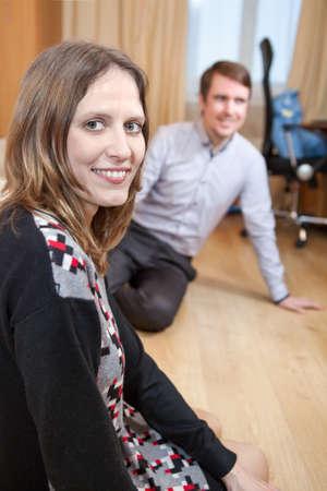 frau sitzt am boden: Junge Frau sitzt Stock in Wohnraum mit Mann im Hintergrund