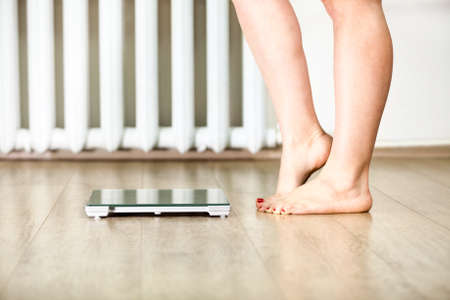 Caucasian female legs standing in front of weight scales hesitating to stand