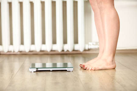 Human legs standing near floor weight scale for weighing Stock Photo