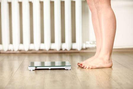 Piernas humanas de pie cerca de la escala de peso piso para pesar Foto de archivo - 37662951