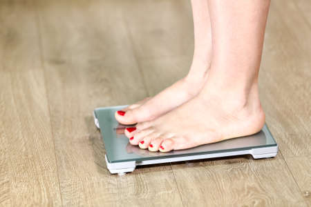Close-up Caucasian legs standing on the floor scale
