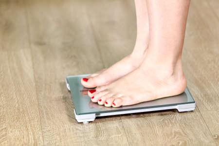 balanza: Primer plano piernas caucásicas de pie en la báscula de piso