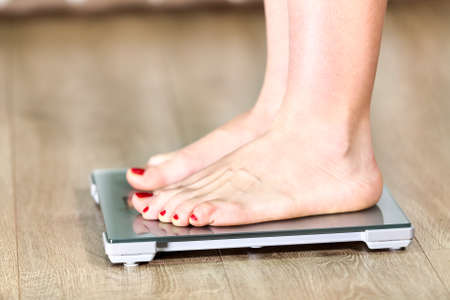 weight room: Close up of Caucasian woman with bare feet is on floor weight scales