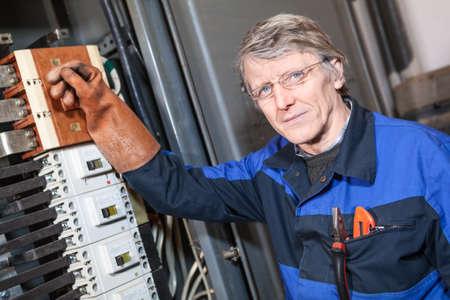 electricista: Superior reparador servicio eléctrico apagando conmutador principal en el panel