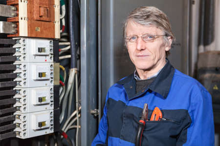 work wear: Electrician repairman in work wear standing near high voltage box Stock Photo
