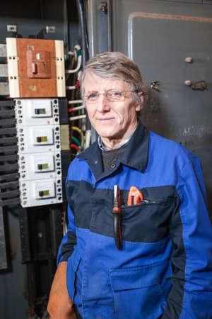 blu: Senior electrician in blu uniform standing near high voltage panel
