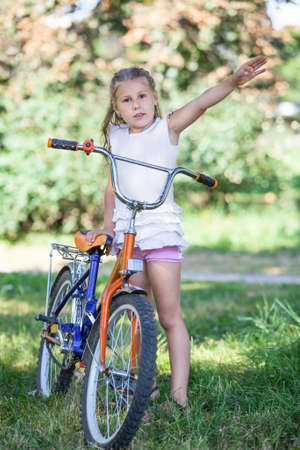Young girl seven years standing with bicycle in the park photo