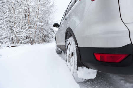 Rear view of snow tires of car driving over snowdrift, winter season