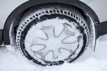 stuck up: Covered with snow winter tired wheel of car