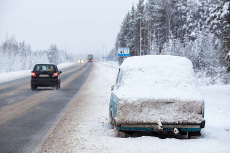 abandoned car: Abandoned car and snow covered on the side of a winter road, covered with snow. The \Kola\ route in north of Karelia, Russia Stock Photo