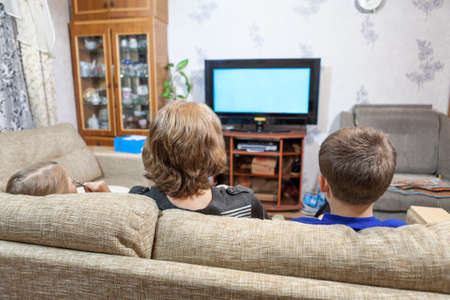 Mother with two children sitting on couch and watching tv at home
