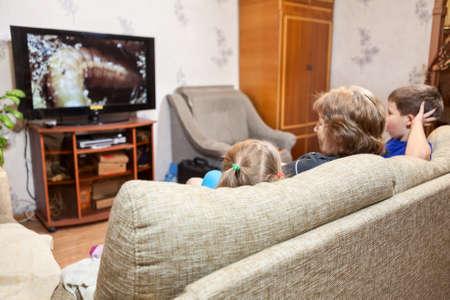 Mensen kijken TV thuis, moeder en haar twee kinderen een meisje en een jongen