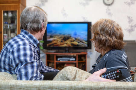Senior Caucasian couple sitting in front of TV and watching screen photo