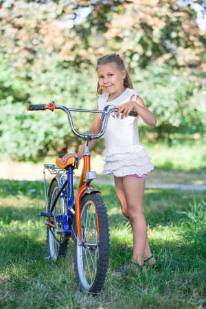 Young girl in the summer park on the grass next to bicycle photo