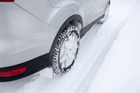 winter tyre: Car wheel in winter tyre driving on snow, close up Stock Photo
