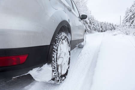 Winter tyres wheels of car on snowy country road photo