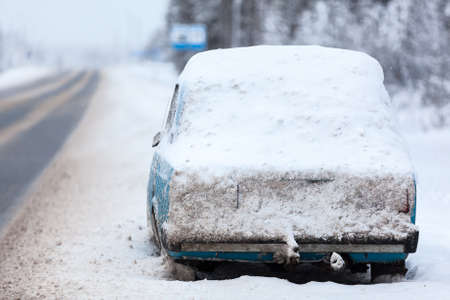 abandoned car: Broken abandoned car covered with snow and ice is on roadside at winter higway in north of Russia