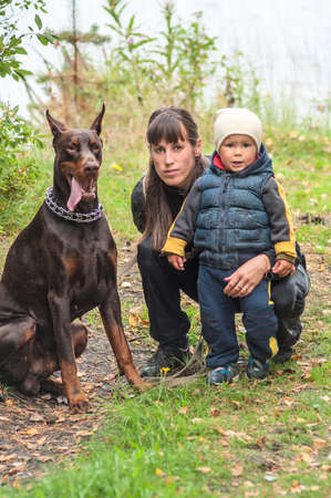 Young woman with her son and doberman dog on walk in autumn park photo