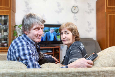 couple couch: Senior Caucasian couple sitting in front of TV and turning back on couch Stock Photo