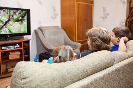people watching tv: Family at home, watching lcd tv sitting on sofa, three people Stock Photo