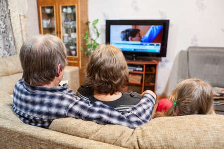family activities: Caucasian father, mother and daughter sitting on the couch and watching tv set Stock Photo