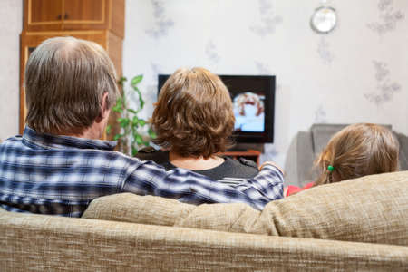 Caucasian father, mother and daughter sitting on the couch and watching tv, rear view photo
