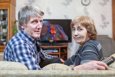 Middle-aged man and woman sitting in front of TV turning back on couch photo