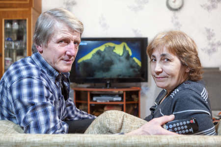 Senior man and woman sitting in front of TV turning back on couch photo