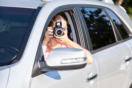 spy girl: Woman sitting in car and photographing with camera at sunny day