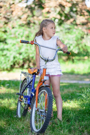 Preteen Caucasian girl standing in summer park with cycle photo