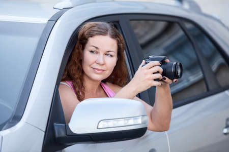 Beautiful woman in car window holding slr camera for photographing photo
