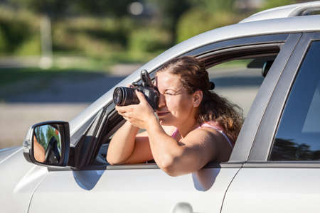 spy girl: Woman a photojournalist making picture with dslr camera leaning out the car