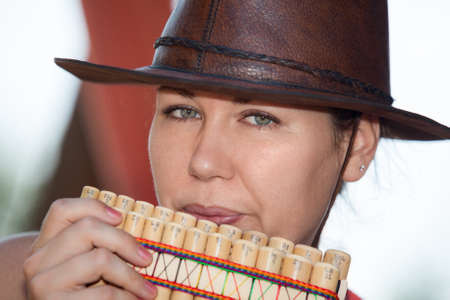panpipe: Young country woman in cowboy hat playing the panpipe