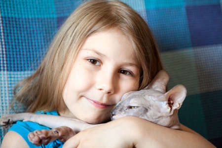 bald girl: Portrait of happy smiling Caucasian small girl hugging a bald cat, close up view