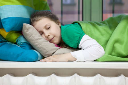 sill: Close up of Caucasian girl sleeping on window sill with bright color pillows and blanket