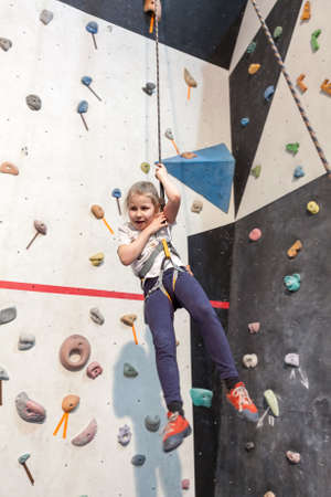 recreational climbing: Small Caucasian girl hanging on the safety rope after rock climbing and falling down Stock Photo