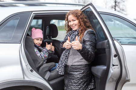 fastening: Caucasian mother showing thumbs up after fastening her daughter with seatbelt in car infant chair Stock Photo
