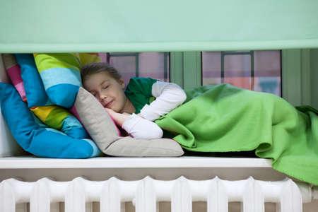 radiador: Muchacha caucásica durmiendo en alféizar de la ventana de plástico con almohadas de colores brillantes y una manta, radiador de calefacción Foto de archivo