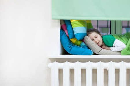 radiador: Niño caucásico durmiendo en ropa en el alféizar de la ventana, copyspace Foto de archivo