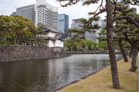 moat wall: TOKYO, JAPAN - CIRCA APR, 2013: Surrounding gardens of the Tokyo Imperial Palace with the moat with stone wall. The Tokyo Imperial Palace is the main residence of the Emperor of Japan Editorial