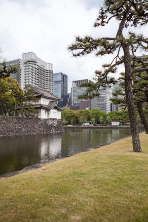 moat wall: TOKYO, JAPAN - CIRCA APR, 2013: Surrounding gardens of the Tokyo Imperial Palace with the moat with stone wall and iron bridges. The Tokyo Imperial Palace is the main residence of the Emperor of Japan Editorial