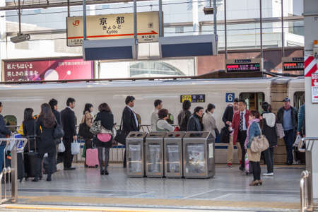 public transfer: TOKYO, JAPAN - CIRCA APR, 2013: People stand in queue for boarding the Hikari Shinkansen to the Kyoto city. The Tokyo Station is a railway station in the Marunouchi district of Chiyoda